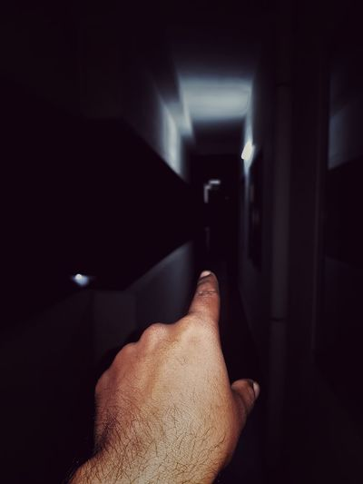 Cropped hand pointing at dark corridor