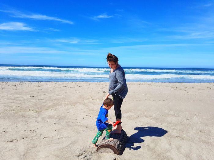 Siblings Playing At Sandy Beach Against Blue Sky