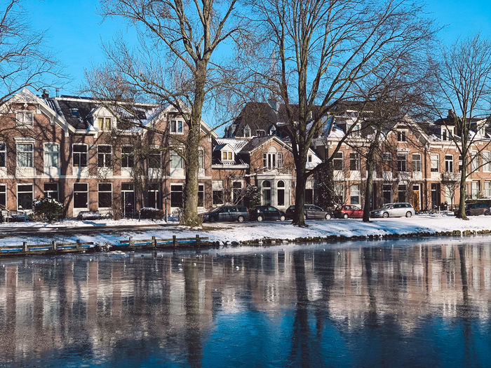 Reflection of bare trees and buildings in canal