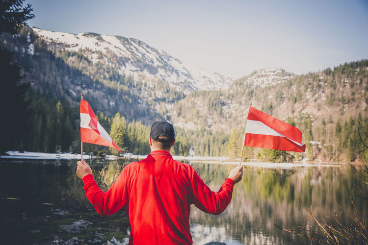 Rear view of man holding flags while standing by lake