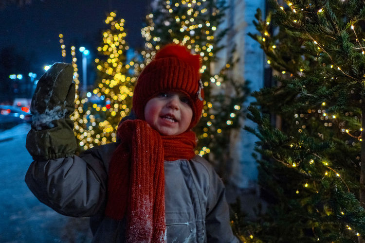 Portrait of smiling boy in illuminated christmas tree during winter