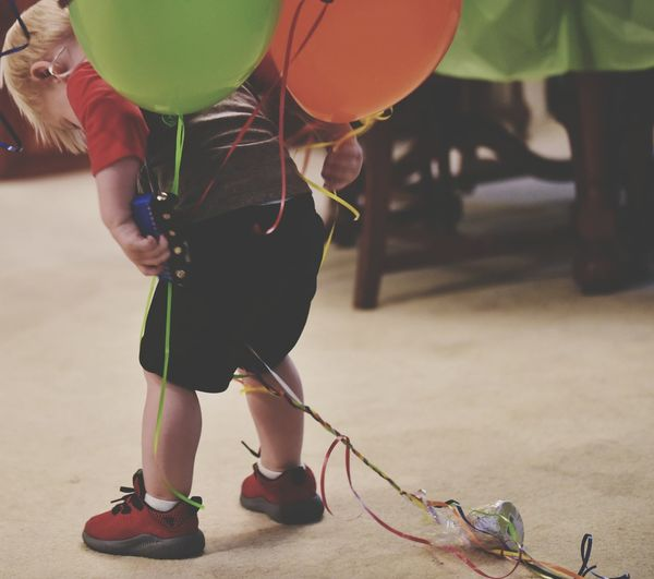 Rear view of boy with helium balloons
