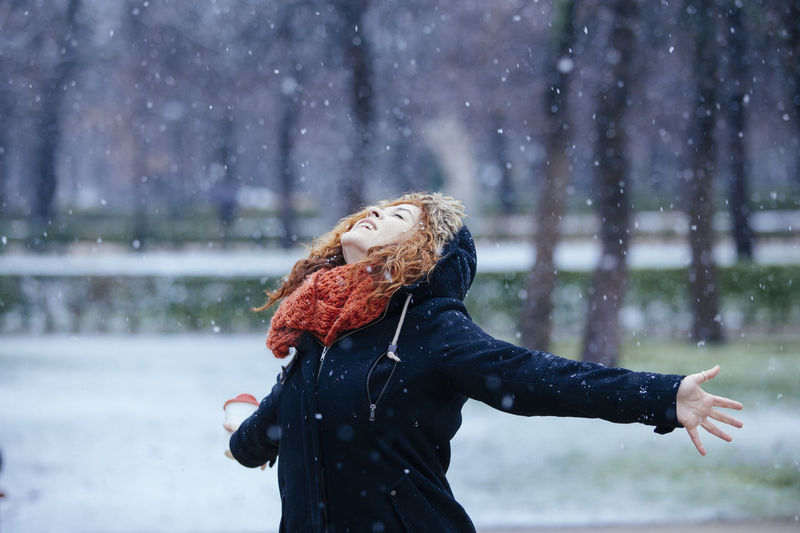 Close-up of woman standing on snow during rainy season