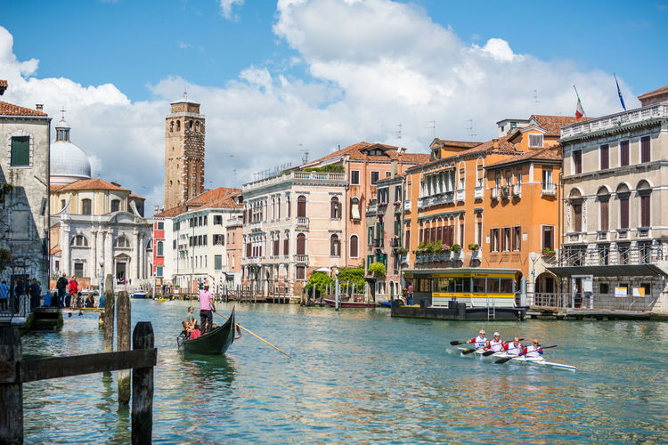People boating in grand canal against buildings