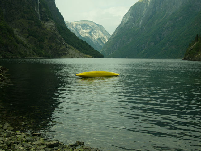 Beauty In Nature Calm Day Idyllic Kayaking Lake Lopsided Majestic Mountain Mountain Range Nature No People Non-urban Scene Outdoors Remote Scenics Sky Tranquil Scene Tranquility Vacations Water Water Surface Waterfront Yellow