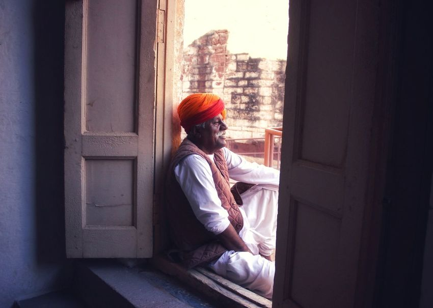 Man sitting peacefully by the door of the fort Head Gear Pagdi Pagdi Indian Safa Rajasthan Rajasthandiaries Rajasthani Jodhpur Jodhpur Fort Leisure Activity Smiling Photography Royal Photographysouls India Indianphotography Classics Art Tourist Destination Fort ForTheLoveOfPhotography EyeEm Selects Sitting Looking Through Window Window Full Length Living Room Door Thoughtful Day Dreaming Thinking First Eyeem Photo
