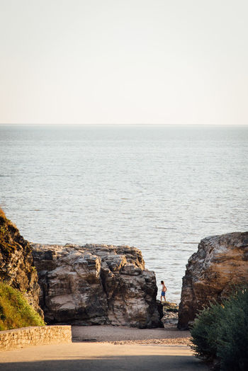 Scenic view of sea with shirtless man seen through rocks against clear sky