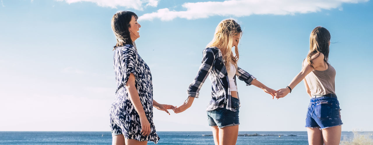 Friends Holding Hands While Standing By Sea Against Blue Sky During Sunny Day
