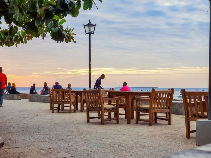People sitting on table at beach against sky during sunset