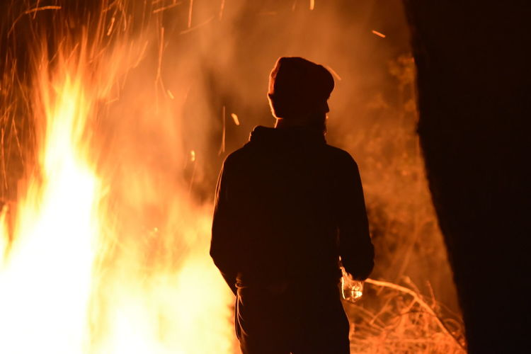 Rear view of silhouette man against fire at night
