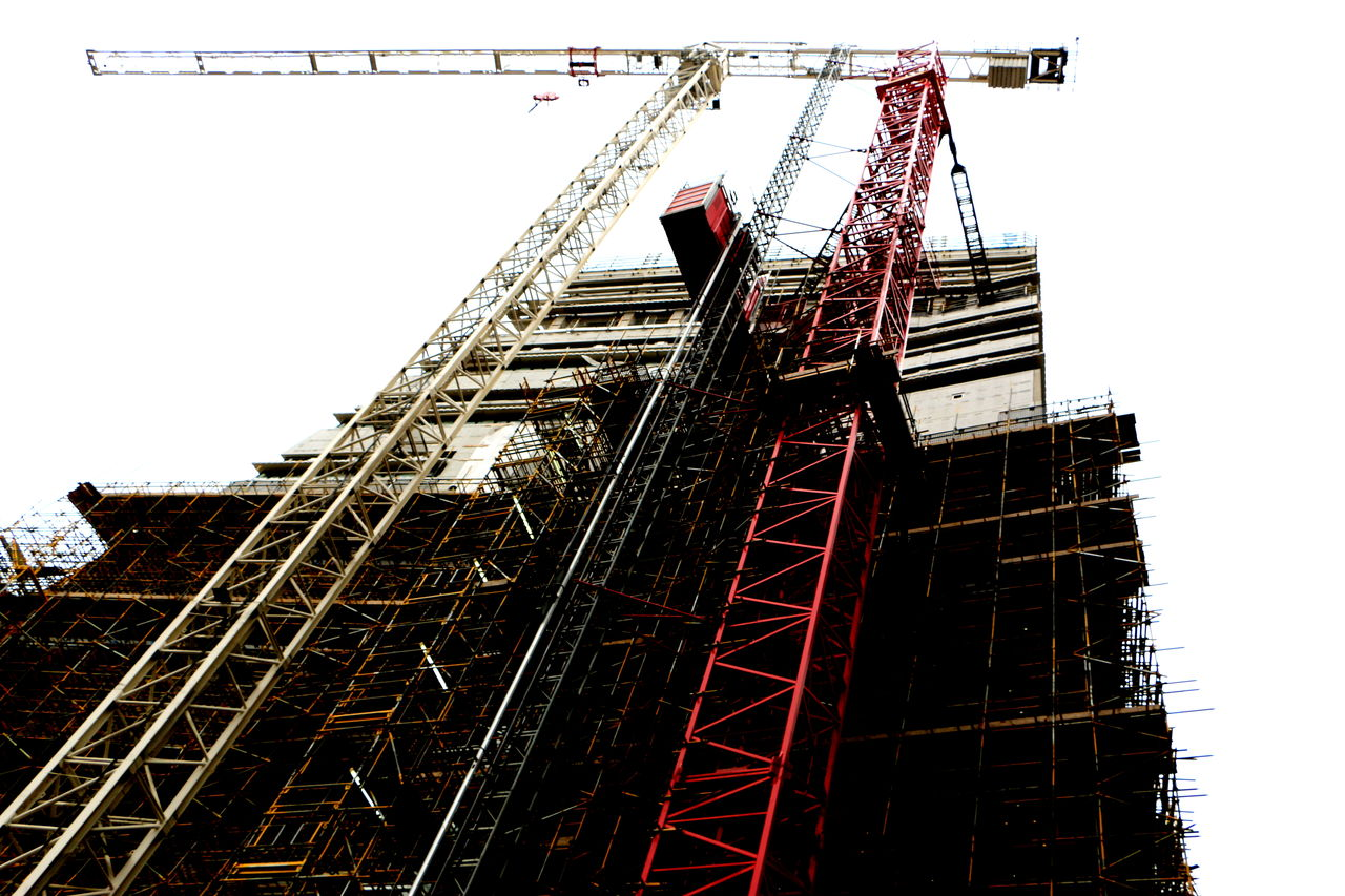 construction site, low angle view, architecture, construction, development, crane - construction machinery, industry, built structure, crane, progress, construction machinery, no people, outdoors, day, construction frame, building exterior, clear sky, building - activity, girder, sky
