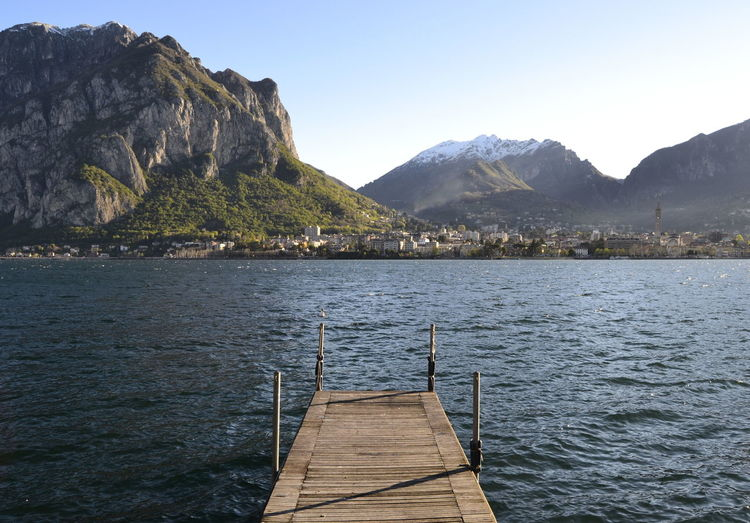 Pier over lake by mountains against sky