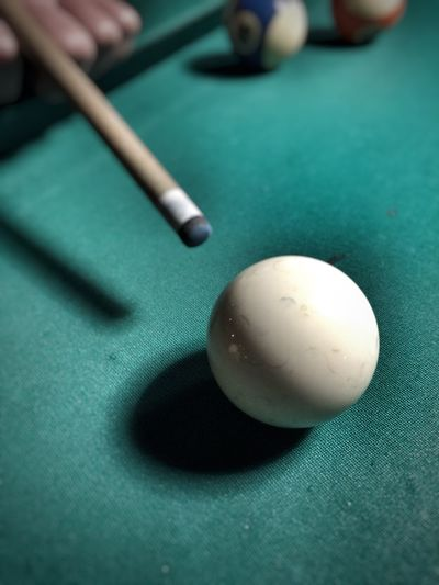 Close-up of pool balls and cue on table