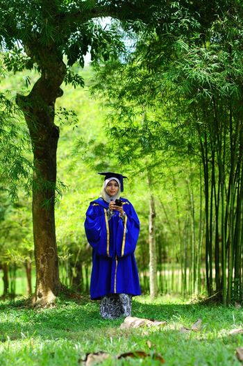 Portrait of woman wearing graduation gown while standing in forest