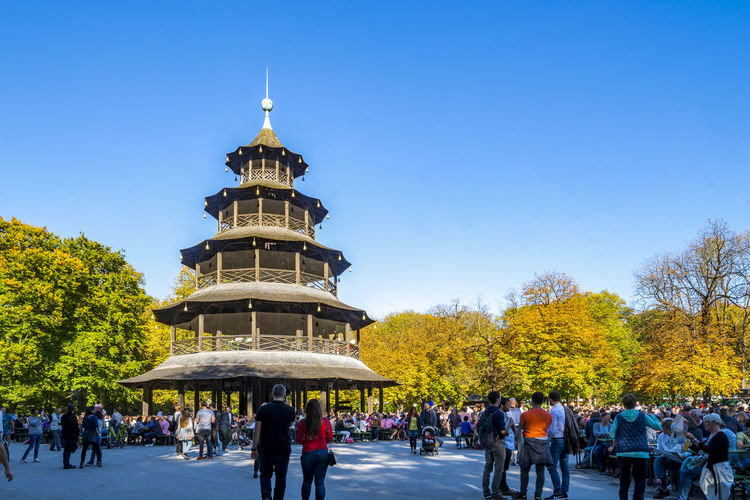 People at park against clear blue sky during autumn