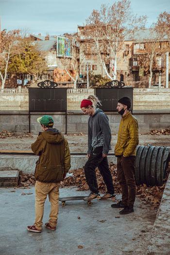 Rear view of people standing on sidewalk in city