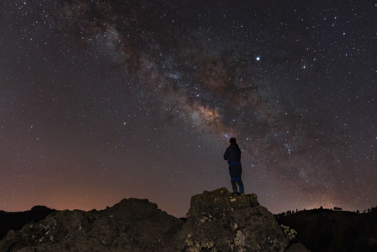 Man standing on rock against star field at night