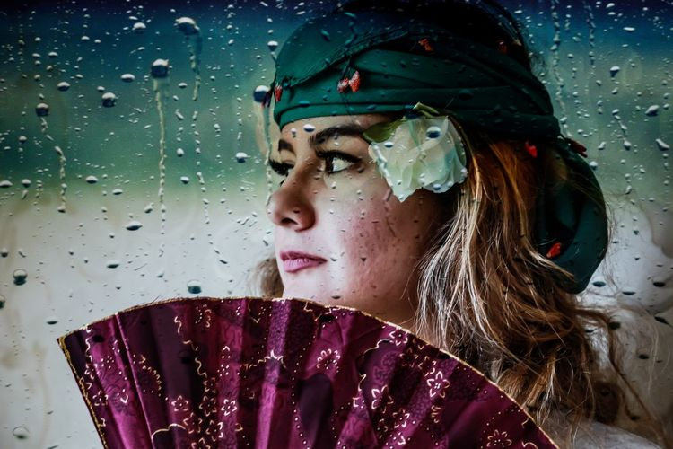 Close-Up Of Young Woman With Folding Fan Seen Through Wet Glass Window