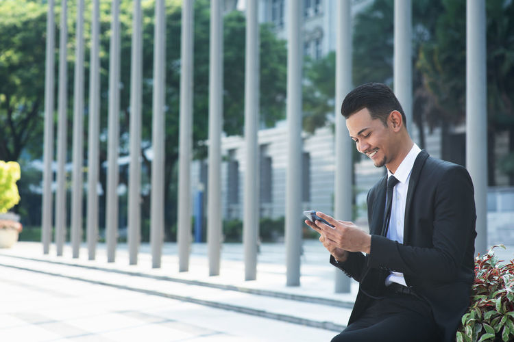 Businessman using phone outdoors