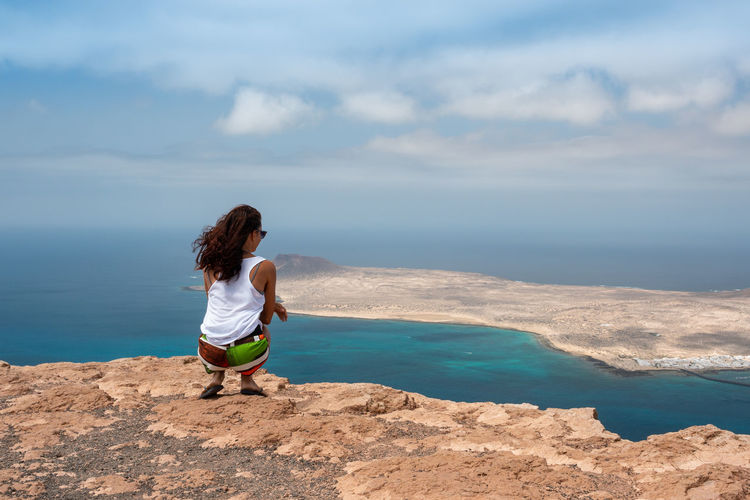 Rear view of mid adult woman looking at sea while crouching on mountain against sky