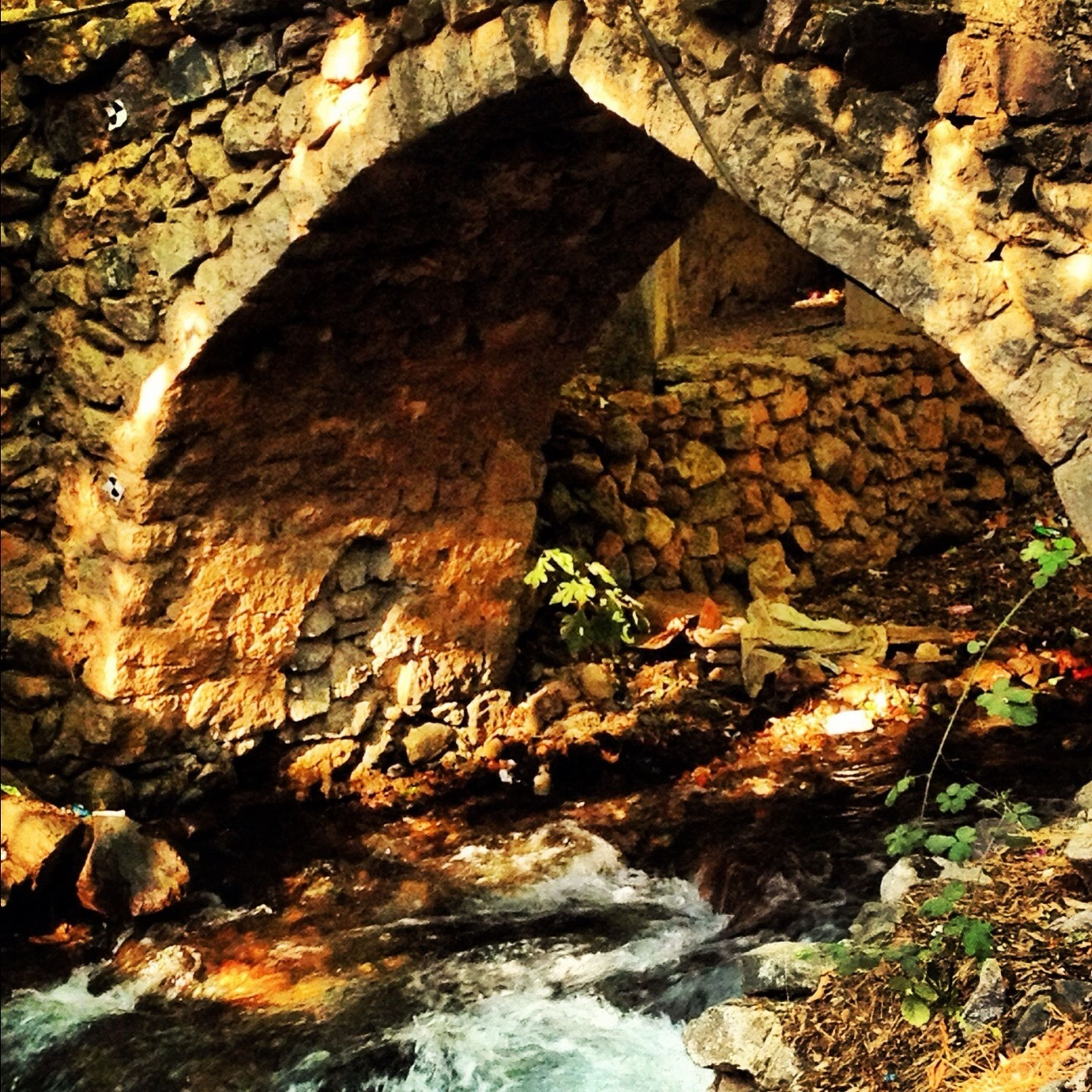 rock - object, water, built structure, stone wall, architecture, rock formation, stone - object, stone, stream, nature, sunlight, rock, river, day, arch, outdoors, flowing, tree, no people, reflection