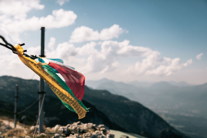 Multi colored flag on mountain against sky