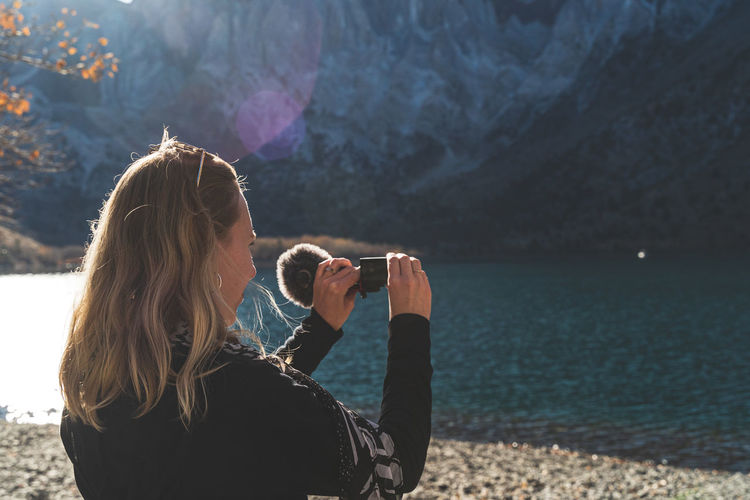 Woman standing in front of beautiful mountain lake filming with video camera as sun begins to set