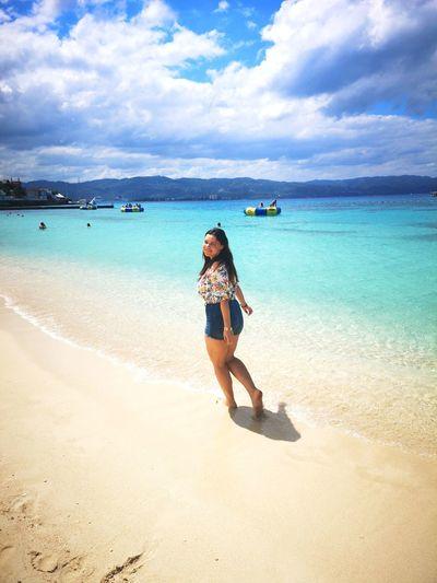 Full length of woman on beach against sky