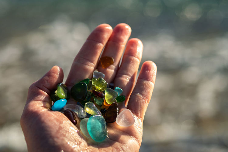Cropped hand of person holding multi colored stones