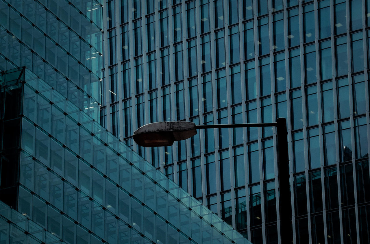 Low Angle View Of Street Light Against Modern Glass Building