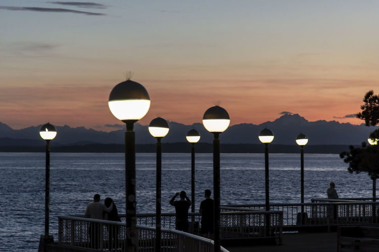 Illuminated lamps on the seattle waterfront after sunset with silhouetted people on a pier