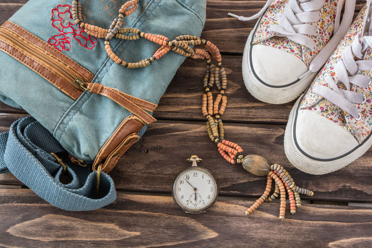 Close-Up Of Shoes With Pocket Watch And Handbag On Table