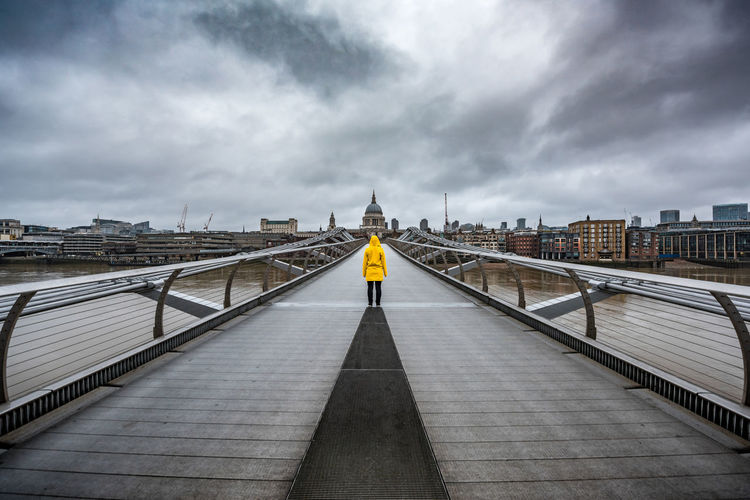 Rear view of person on london millennium footbridge leading towards st paul cathedral