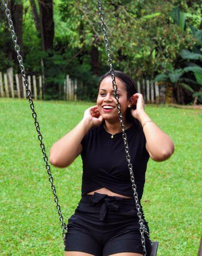Woman sitting on swing in park