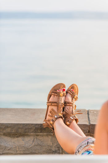 Close up of young woman resting her legs in leather sandals at sea shore, back view with arm and legs of unidentifiable woman in colorful skirt EyeEmNewHere Leather Lifestyle Relaxing Riverside Sandals Seashore Sunlight Woman barefoot Bodensee Leather Sandals Leather Shoes Legs_only Resting