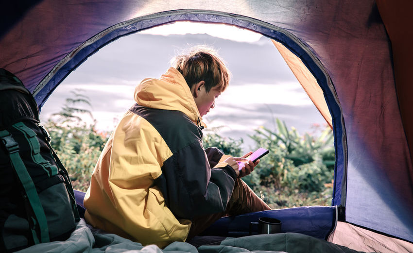 Man using mobile phone while sitting in tent during sunset
