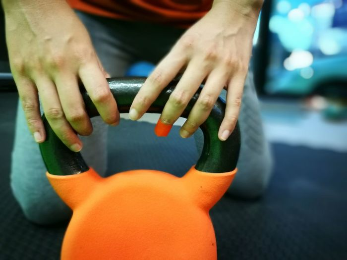 Midsection Of Woman Holding Kettlebell In Gym