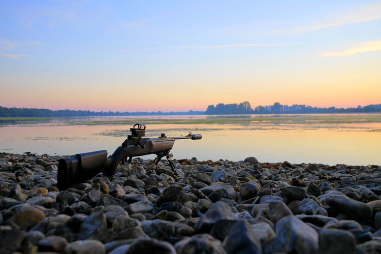 Beach Beauty In Nature Cannon Land Nature Non-urban Scene Orange Color Outdoors Pebble Rifle Rock Rock - Object Scenics - Nature Sea Sky Sniper Solid Stone - Object Sunrise Sunset Surface Level Tranquil Scene Tranquility Water Weapon