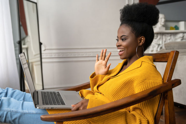 Close-up of smiling woman using laptop sitting on chair at home