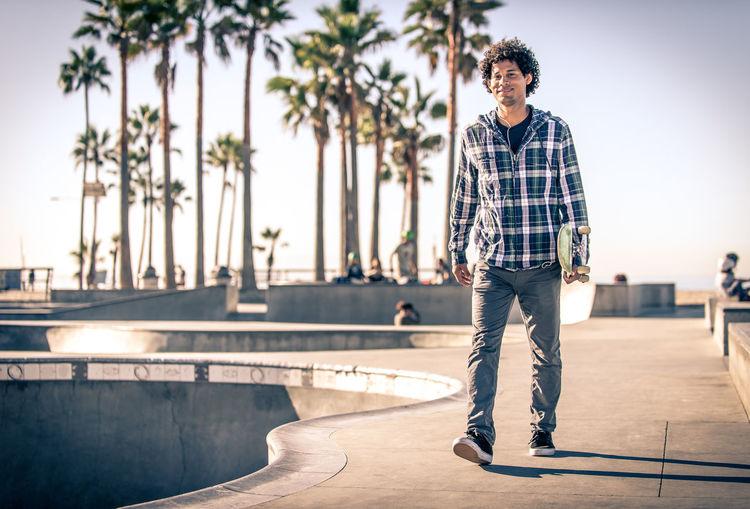 Full length portrait of man walking at skateboard park