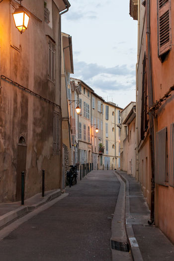 A narrow street at the Old town, Aix-en-Provence Architecture Building Building Exterior Built Structure City Cloud Cloud - Sky Diminishing Perspective Empty Road Footpath Illuminated Long Narrow No People Outdoors Residential District Road Sky Street Street Light The Way Forward
