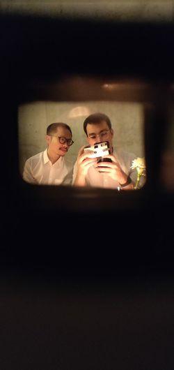 Man Taking Selfie In Mirror Reflection With Friend