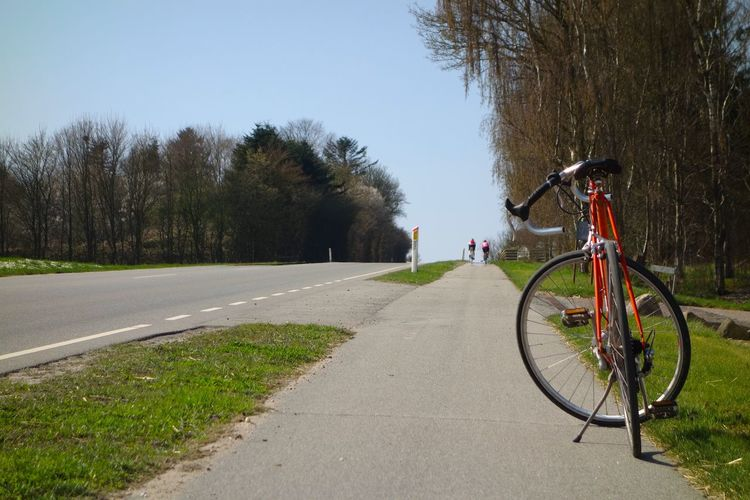 Bicycle on road against clear sky