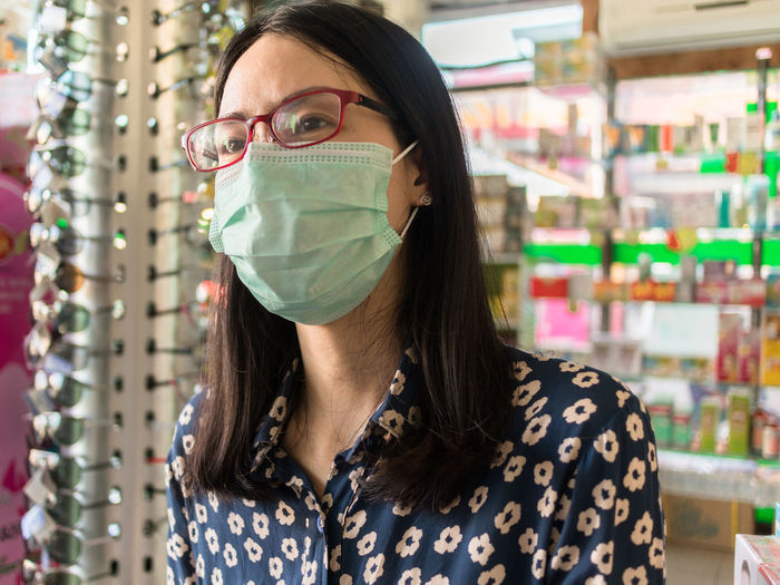 Young woman wearing surgical mask at shop