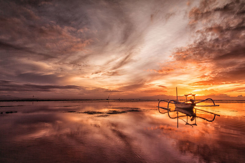 Outrigger boat at beach against cloudy sky during sunset