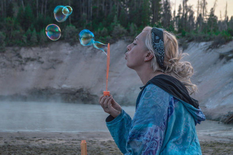 Side view of young woman blowing bubbles at beach