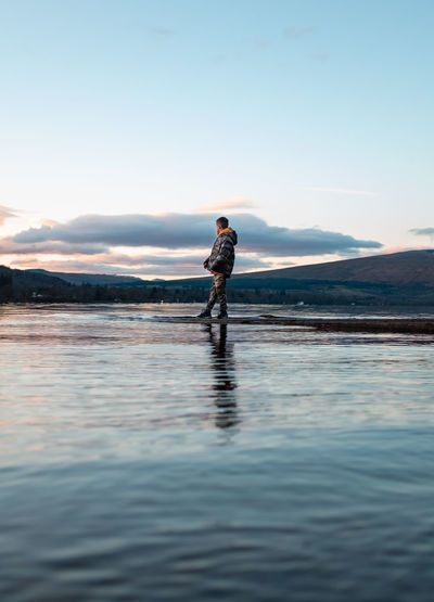 Side view of boy standing by lake against sky