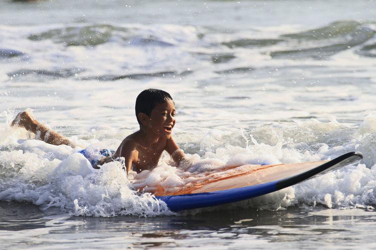 Full length of shirtless boy in sea