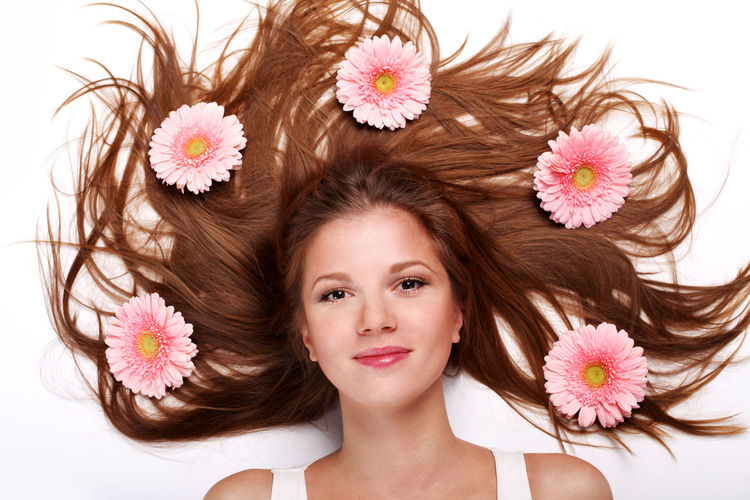 Portrait of woman lying with pink flowers against white background