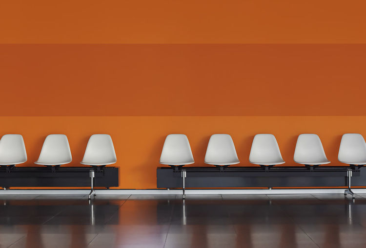 Empty chairs and table against orange wall